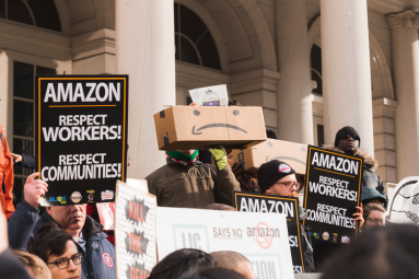 Protesters hold Amazon: Respect Workers signs