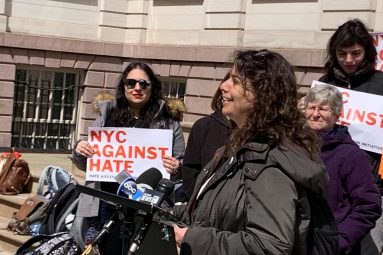 JFREJ members gather outside holding NYC Against Hate signs