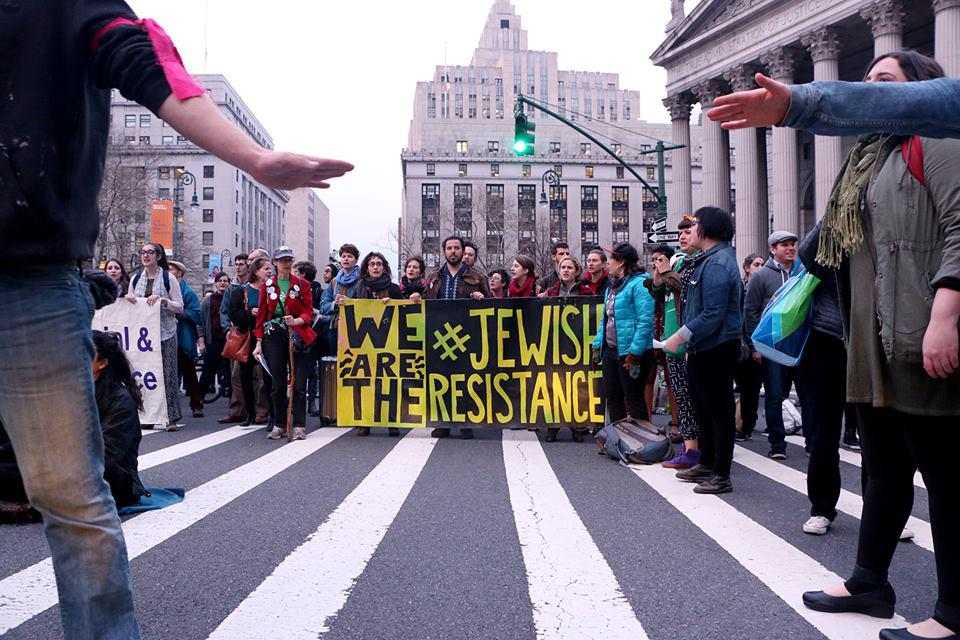 Protesters gather behind a sign saying We Are The Jewish Resistance