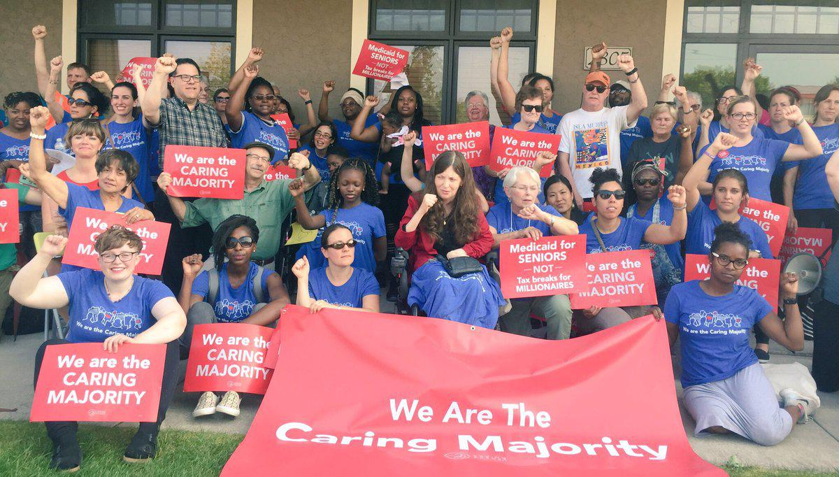Members of the caring majority caucus gather with matching shirts and signs saying We Are The Caring Majority
