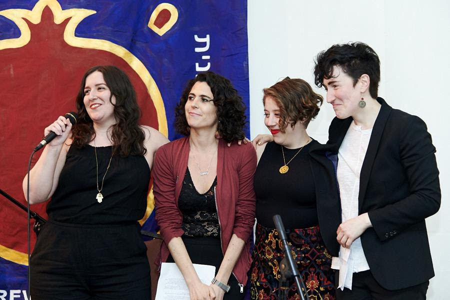 Four women stand in front of a banner while one speaks into a microphone