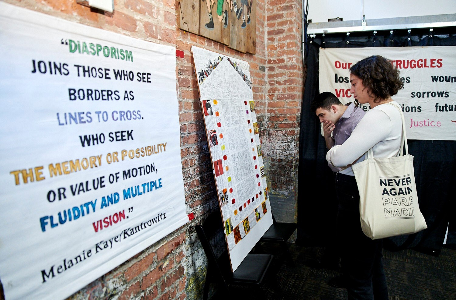 """Image of two people looking at a banner and a poster. The banner reads """"Diasporism joins those who see borders as lines to cross. Who seek the memory or possibility or value of motion, fluidity and multiple vision. - Melanie Kaye/Kantrowitz"""""""